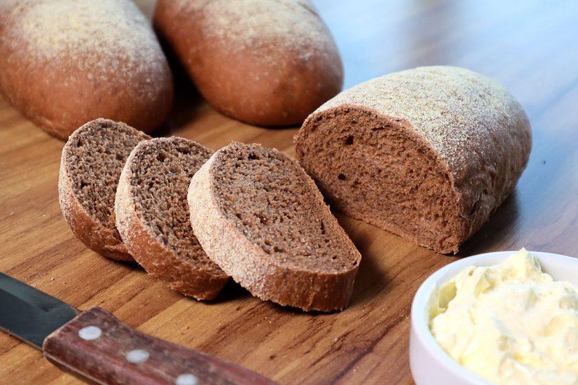 Um pão australiano fatiado com uma manteiga aerada e uma faca ao lado